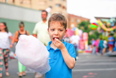 cotton candy: Portrait of cute child eating cotton candy over a summer fair festival background Stock Photo
