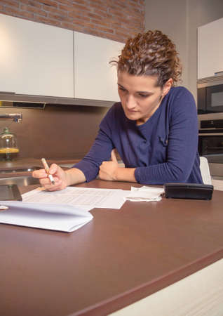 Unemployed and divorced woman with many debts reviewing her monthly bills photo