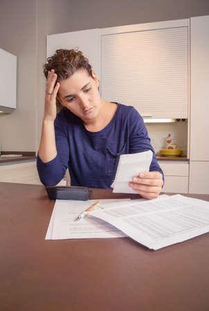 Arbeitslose und geschiedene Frau mit vielen Schulden der Überprüfung ihre Monatsrechnungen Standard-Bild