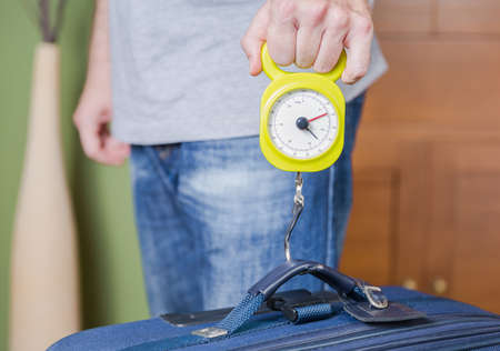 restrictions: Man checking hand luggage weight using a steelyard balance by low cost airlines restrictions