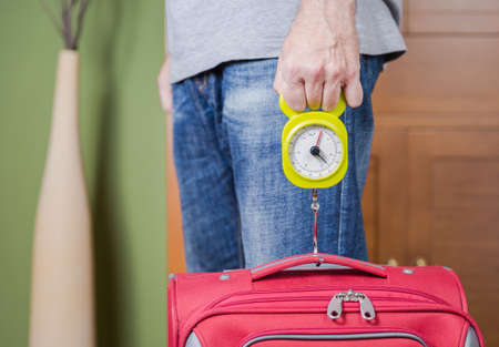 steelyard: Man checking hand luggage weight using a steelyard balance by low cost airlines restrictions