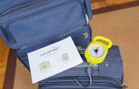 steelyard: Low cost airlines luggage restrictions and baggage ready to weight with a steelyard balance on the background