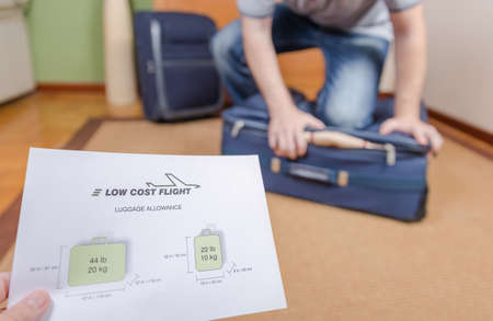 restrictions: Man trying to close full hand luggage for comply low cost airlines restrictions Stock Photo