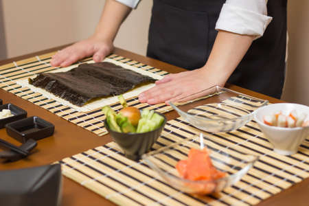 Woman chef ready to prepare japanese sushi rolls, with principal ingredients in the foreground  Selective focus in nori seaweed photo