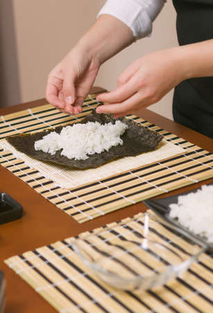 Hands of woman chef filling japanese sushi rolls with rice on a nori seaweed sheet photo