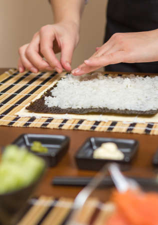 Hands of woman chef filling japanese sushi rolls with rice on a nori seaweed sheet  Selective focus in sushi roll  photo