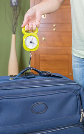 steelyard: Woman checking hand luggage weight using a steelyard balance by low cost airlines restrictions