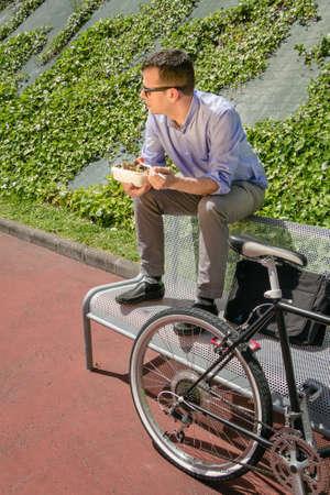 banc de parc: Jeune homme d'affaires de manger une salade à la pause déjeuner assis sur un banc à l'extérieur