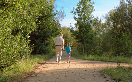 Back view of grandfather and grandchild walking on a nature path
