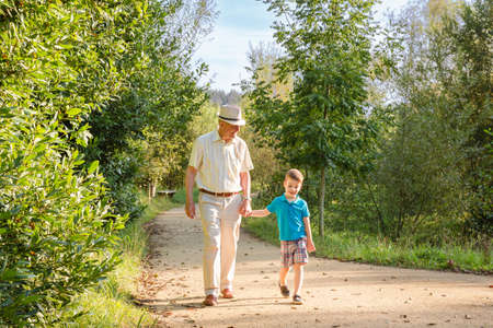 grandparent: Front view of grandfather with hat and grandchild walking on a nature path Stock Photo