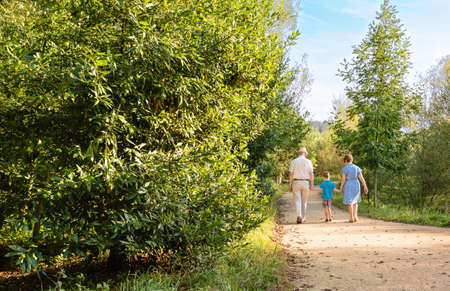 Back view of grandparents and grandchild walking on a nature path photo