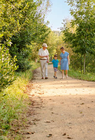 grandmother grandchild: Front view of grandparents and grandchild walking on a nature path Stock Photo