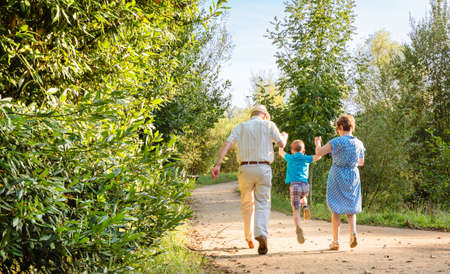 Back view of grandparents and grandchild jumping on a nature path