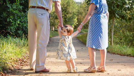 granny and grandad: Portrait of baby granddaughter walking with her grandparents on a nature path