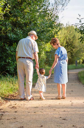 three: Back view of grandparents and baby grandchild walking on a nature path