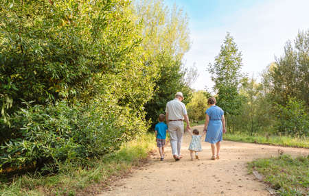 Back view of grandparents and grandchildren walking on a nature path