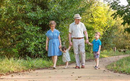 Front view of grandparents and grandchildren walking on a nature path photo