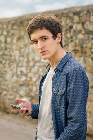 Portrait of hipster teenager using his smart phone outdoors photo