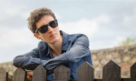 glass fence: Portrait of hipster teenager with sunglasses posing outdoors over a wooden fence Stock Photo