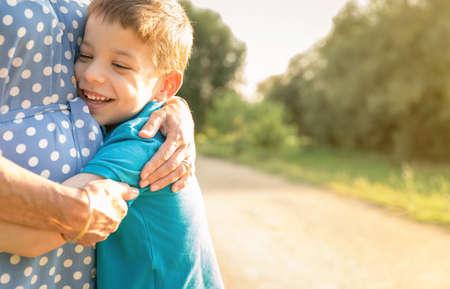 personas abrazadas: Retrato de feliz abrazos nieto abuela sobre un fondo de naturaleza al aire libre Foto de archivo