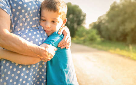Portrait of grandson hugging grandmother over a nature outdoor background Stock Photo