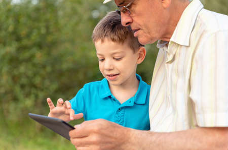 Closeup of grandchild teaching to his grandfather to use a electronic tablet over nature background. Generation values concept. Archivio Fotografico