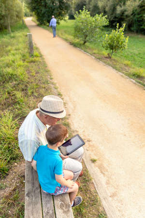 Grandchild teaching to his grandfather to use a electronic tablet on a park bench. Generation values concept. Archivio Fotografico
