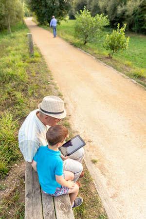 Kleinkind lesgeven aan zijn grootvader naar een elektronische tablet te gebruiken op een bankje. Generation waarden concept.