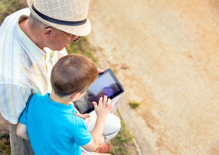 Grandchild teaching to his grandfather to use a electronic tablet on a park bench. Generation values concept. Banco de Imagens