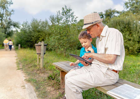 Grandchild teaching to his grandfather to use a electronic tablet on a park bench. Generation values concept. photo