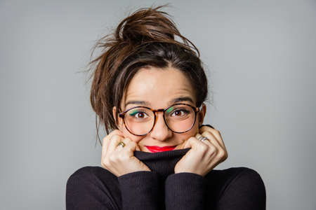 woman sweater: Portrait of real young girl with glasses and red lips taking her black neck sweater with the hands over a gray background