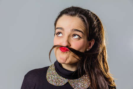 black head and moustache: Portrait of real young girl with red lips using her hair like a funny moustache over a gray background