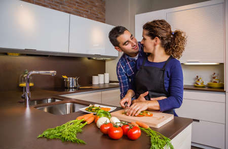 family kitchen: Couple in love hugging and preparing healthy vegetables in the kitchen. Modern family lifestyle concept. Stock Photo