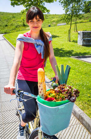 leek: Beautiful young sportive woman with groceries in a basket bike on a sunny summer day Stock Photo