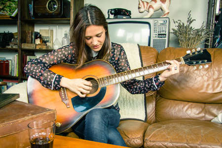 Beautiful young hipster girl playing acoustic guitar sitting in a sofa at home. Retro vintage colors edition photo