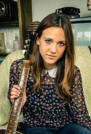 Portrait of beautiful young hipster girl with acoustic guitar sitting in a sofa at home. Retro vintage colors edition photo