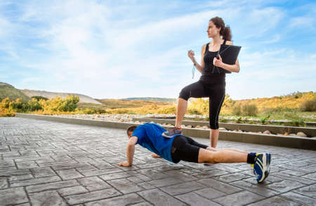 hard core: Beautiful athlete girl coach training very hard a man while timing the push ups with chronometer