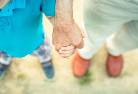 Gyermek gazdaság kezét senior férfi egy természet utat háttérben. Két különböző generációk fogalma.