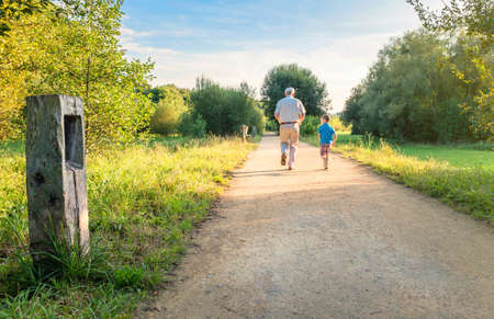 Back view of senior man with hat and happy child running on a nature path. Two different generations concept. Standard-Bild