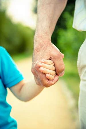 Niño que sostiene la mano del hombre mayor sobre un fondo de naturaleza. Dos generaciones concepto diferente.
