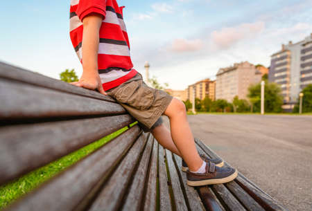 Closeup of boy legs with short pants sitting on the top of wooden bench park relaxing in a bored summer day Stock Photo