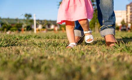 晴れた夏の日の芝生公園で母親と一緒に歩くことを学んで愛らしい赤ちゃん女の子