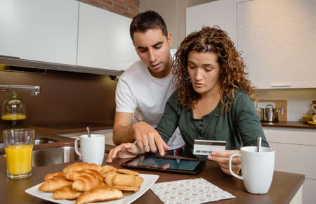 family budget: Portrait of young couple with electronic tablet reviewing credit card monthly payouts Stock Photo