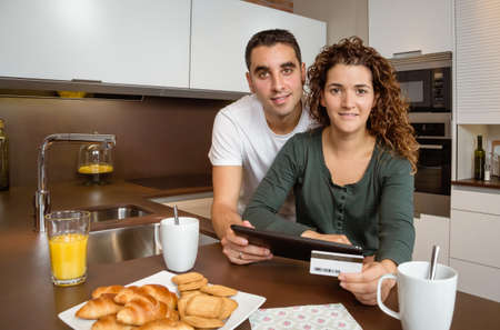 Portrait of young couple with electronic tablet and credit card buying on internet photo
