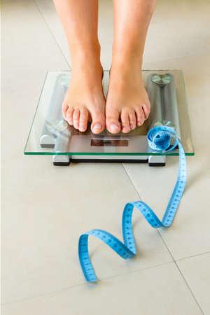 Close up dos pés Mulher que está na escala de banheiro e uma fita métrica. Saúde e conceito de peso.
