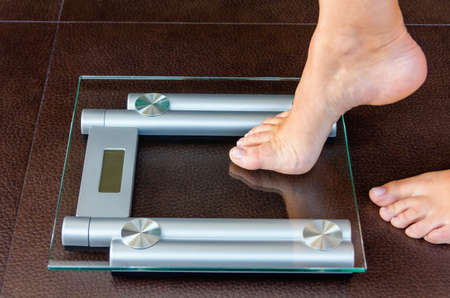 Close-up van de vrouw voet uploaden naar weegschaal. Gezondheid en gewichtsconcept