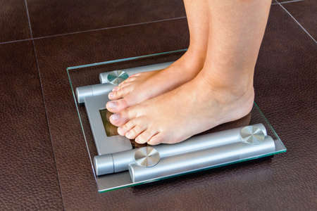 Closeup of woman feet standing on bathroom scale. Health and weight concept.