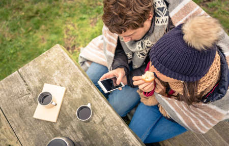 View from above of young beautiful couple under blanket looking smartphone and eating muffin in a cold day with sea and dark cloudy sky on the background