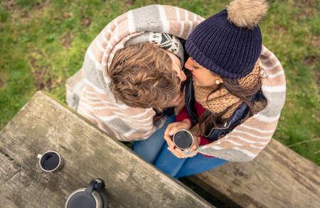 Vue de dessus du jeune couple sous couverture et rayures avec boisson chaude embrassant en plein air dans une journée froide Banque d'images