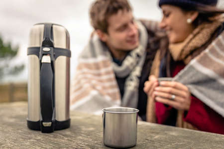 Closeup of metalic cup and thermos with hot beverage in a wooden table with young couple under blanket blurred on the background photo